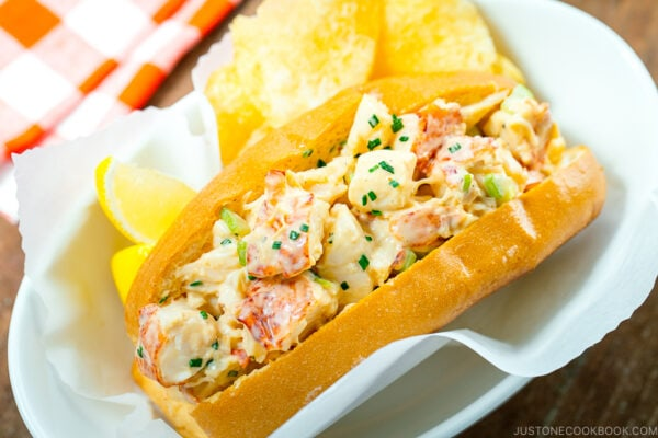 Lobster Roll served in a white dish along with potato chips and lemon.