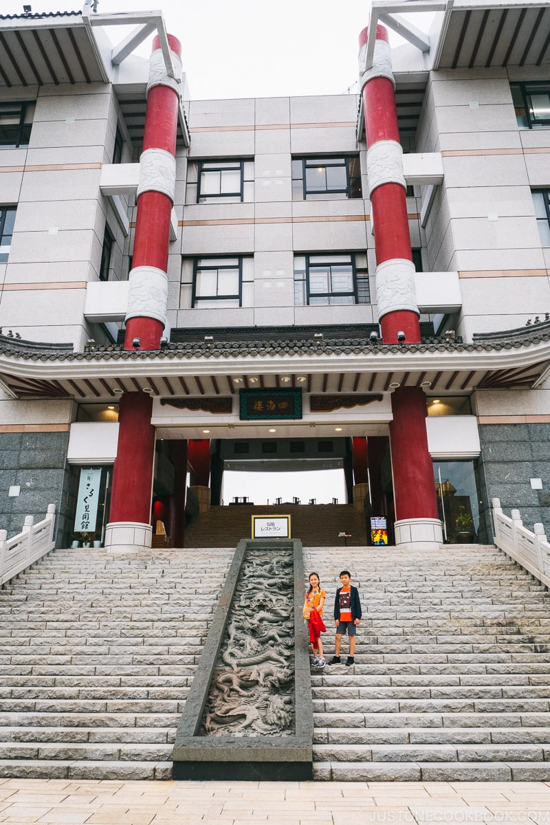 two children on stone steps in front of a building