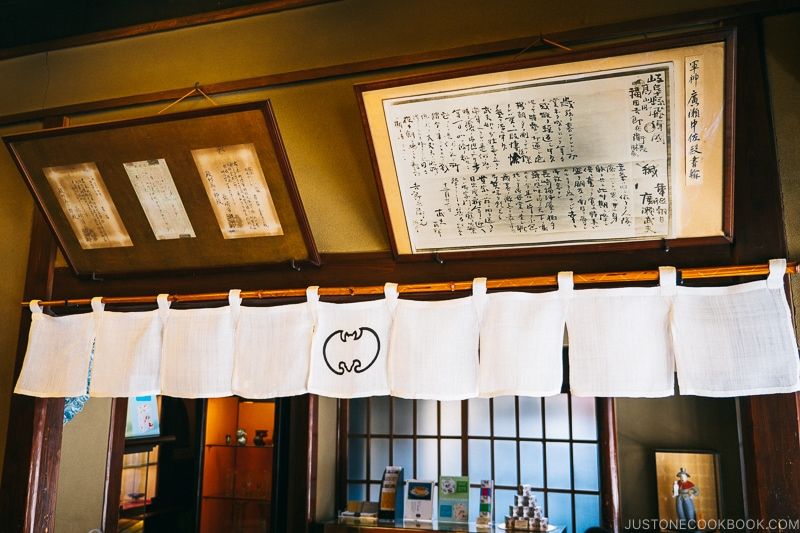 old framed prints hanging on a wall above a white banner with bat