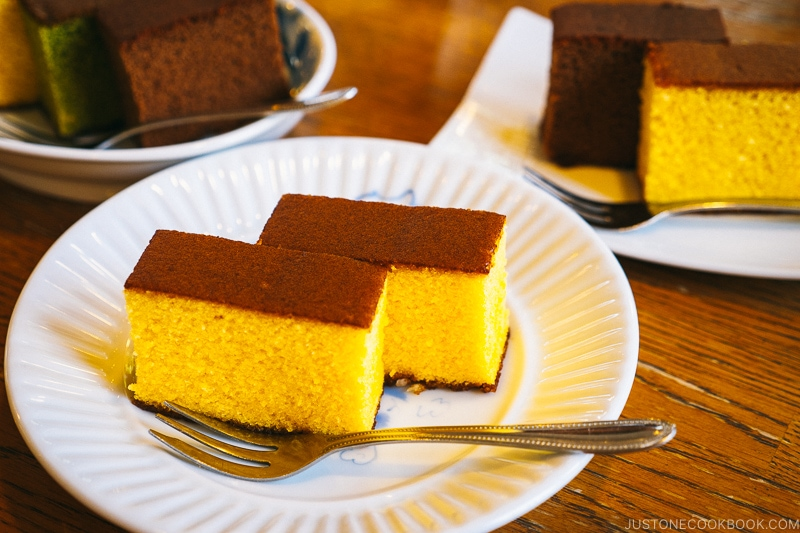 castella cake on a white plate with a fork