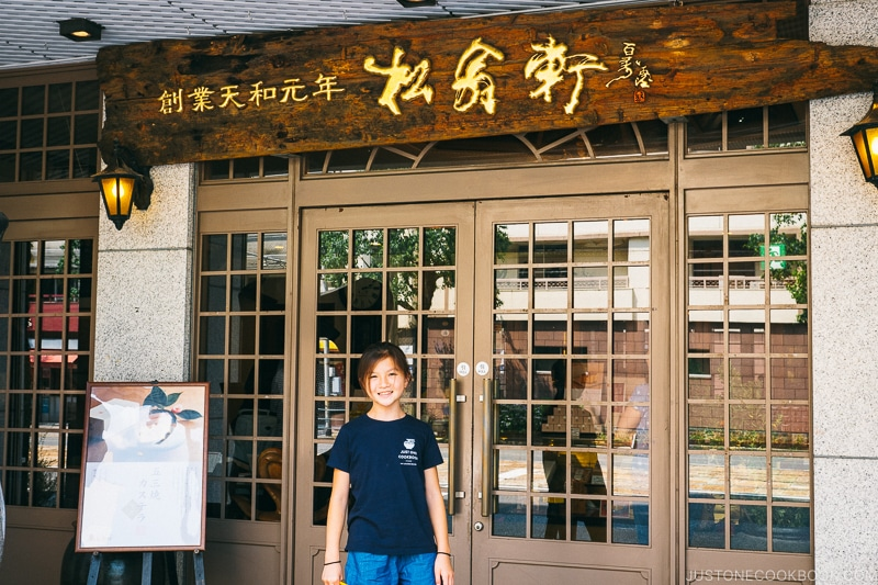 girl standing in front of a Japanese sweets store