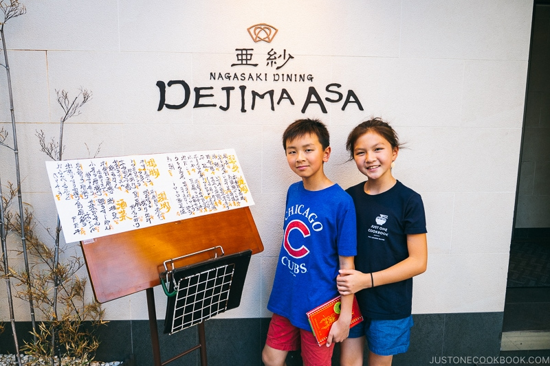 two children standing in front of Dejima Asa sign