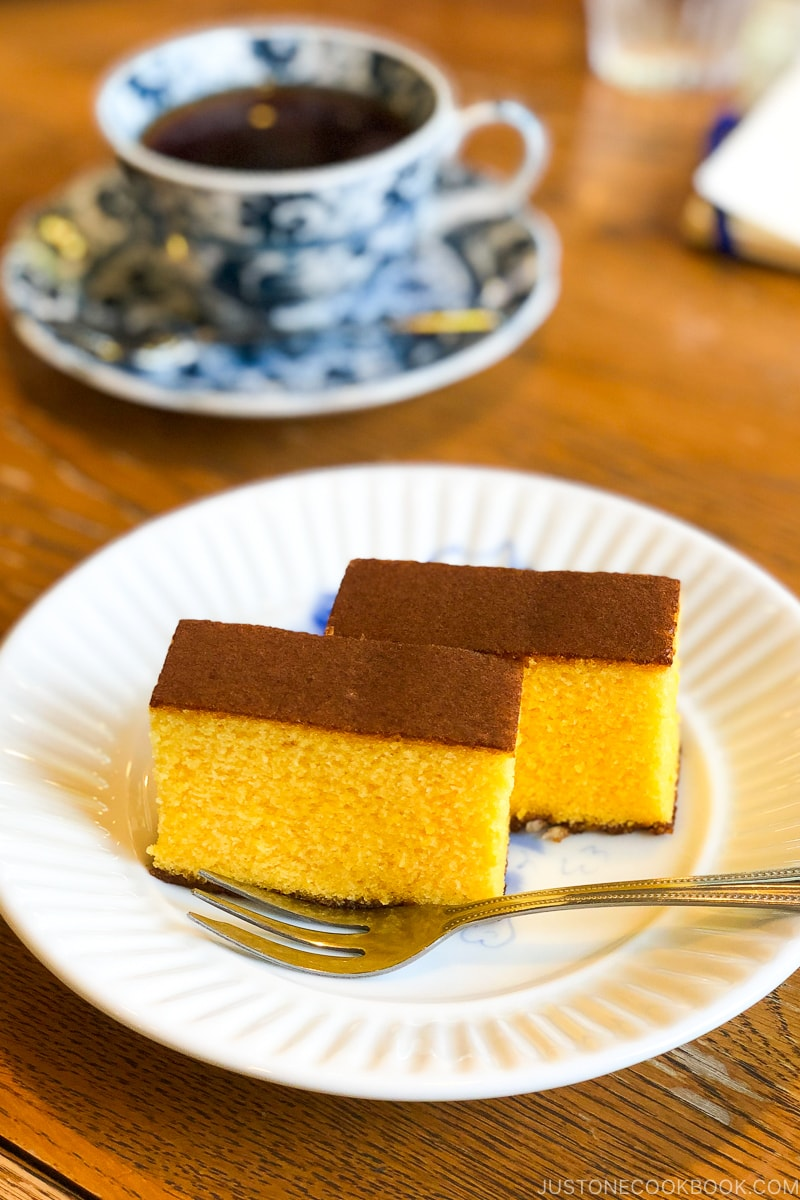 castella cake on a white plate next to a cup of coffee