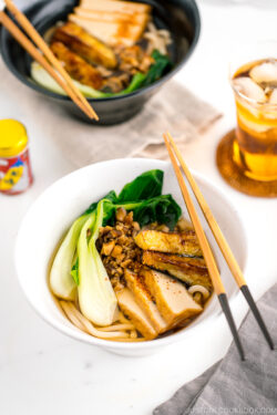 A white bowl containing Vegetarian Udon Noodle Soup topped with bok choy, fried tofu, minced mushroom, and crispy eggplant.