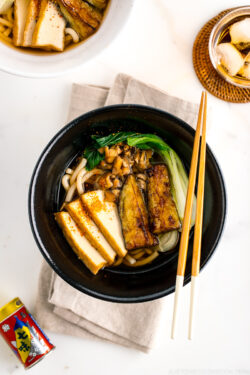 A black bowl containing Vegetarian Udon Noodle Soup topped with bok choy, fried tofu, minced mushroom, and crispy eggplant.