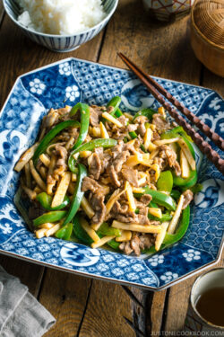 A Japanese blue and white ceramic containing Beef and Green Pepper Stir Fry.