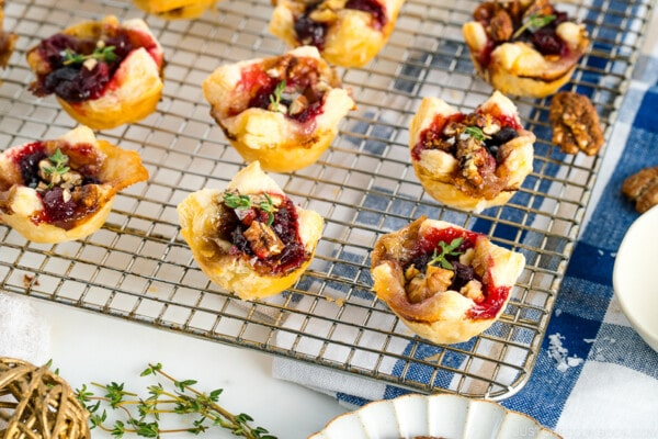 Cranberry Brie Bites placed on a wire rack garnished with thyme.