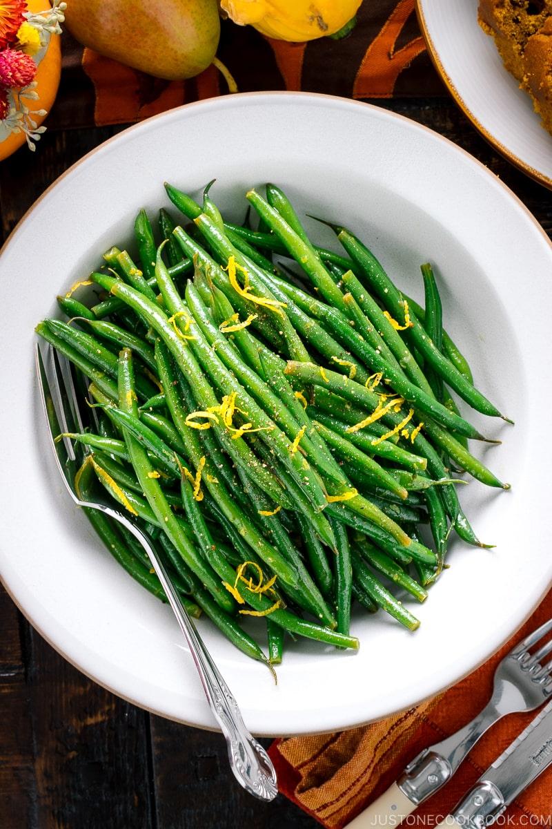 A white bowl containing Green Beans with Yuzu Vinaigrette.