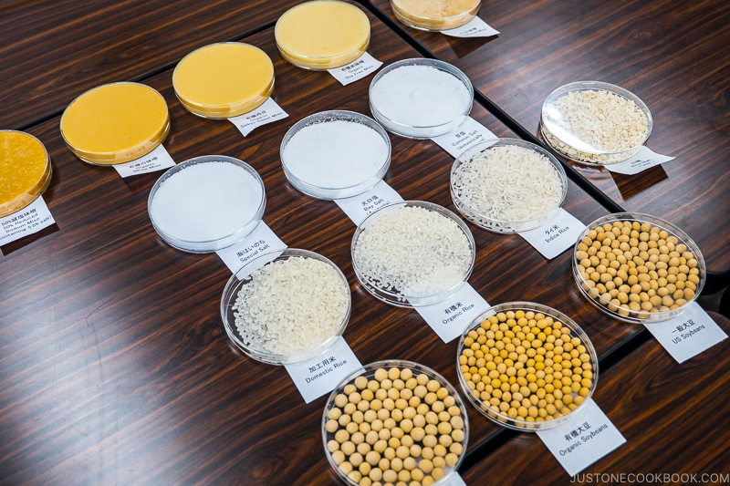 types of miso, salt, rice, and soy bean in clear dishes on tables