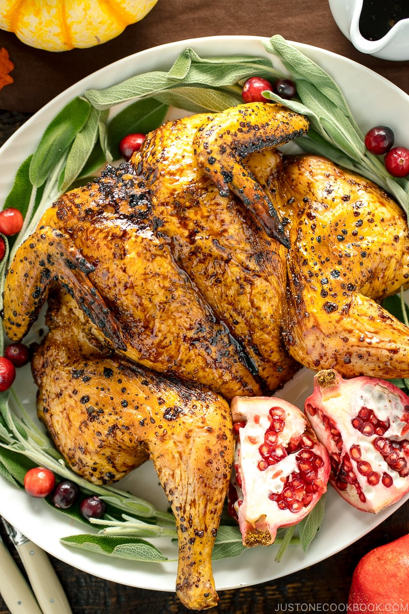 A white platter containing Honey Soy Glazed Spatchcock Chicken decorated with sage, pomegranate, and cranberries.