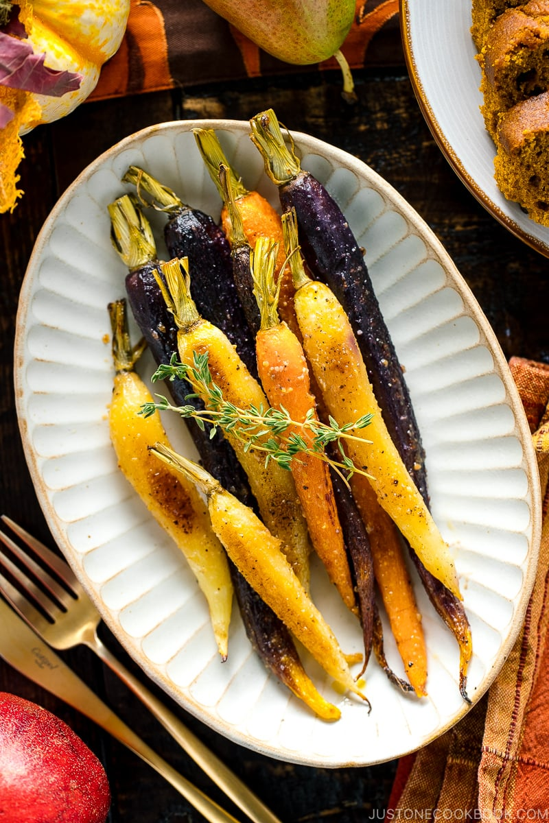 A white ceramic plate containing Maple and Miso Glazed Roasted Carrots.
