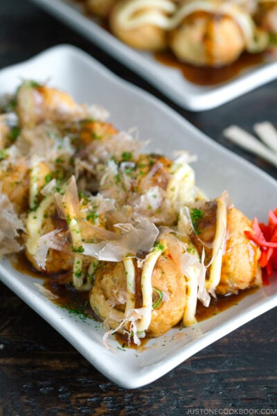 A white plate containing Takoyaki (Octopus Balls) topped with a generous drizzle of takoyaki sauce, Japanese mayo, aonori, katsuobushi.
