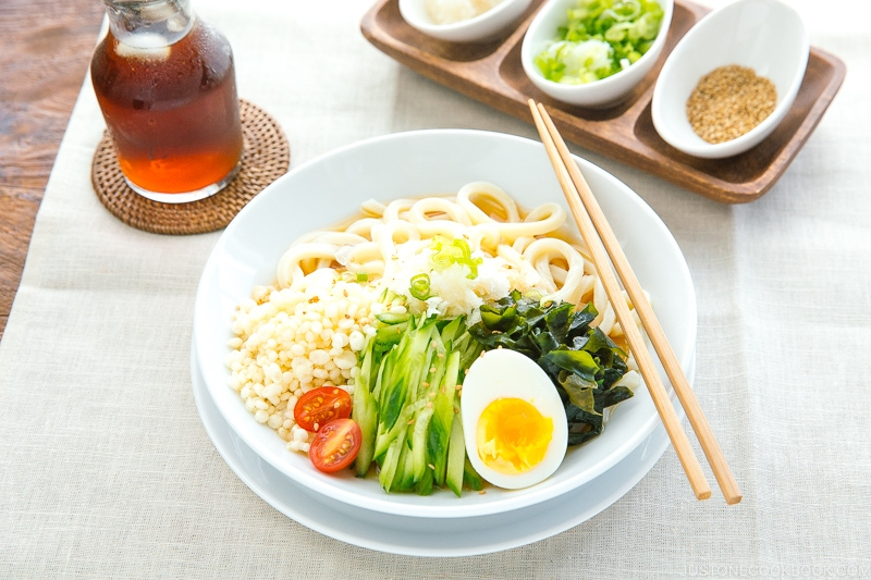 A white bowl containing chilled udon noodles, tenkasu, julienned cucumber, boiled egg, wakame seaweed, and grated onion, along with savory noodle soup.