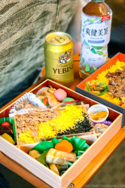 two bento boxes on a train table next to a beer can