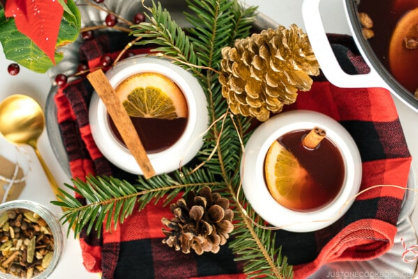 White cups containing hot mulled cider garnished with orange slice and a cinnamon stick.