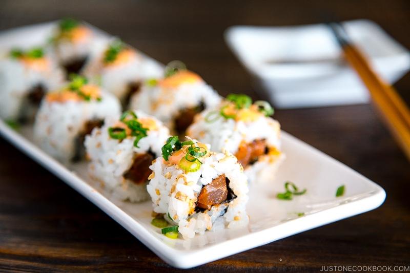 spicy tuna rolls presented on a white rectangular dish