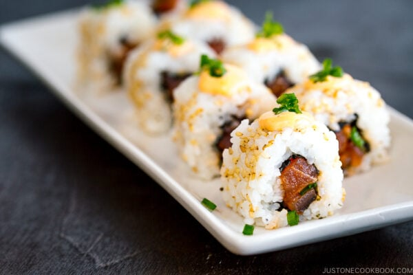spicy tuna roll garnish with sesame seeds and topped with spicy mayo served on a dish