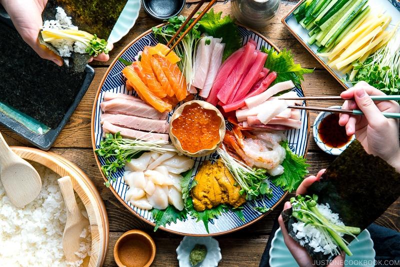 A sashimi platter with varioius sashimi (tuna, salmon, amaebi, uni, scallop, kanpachi, ikura and more), sushi rice, and vegetable platter.
