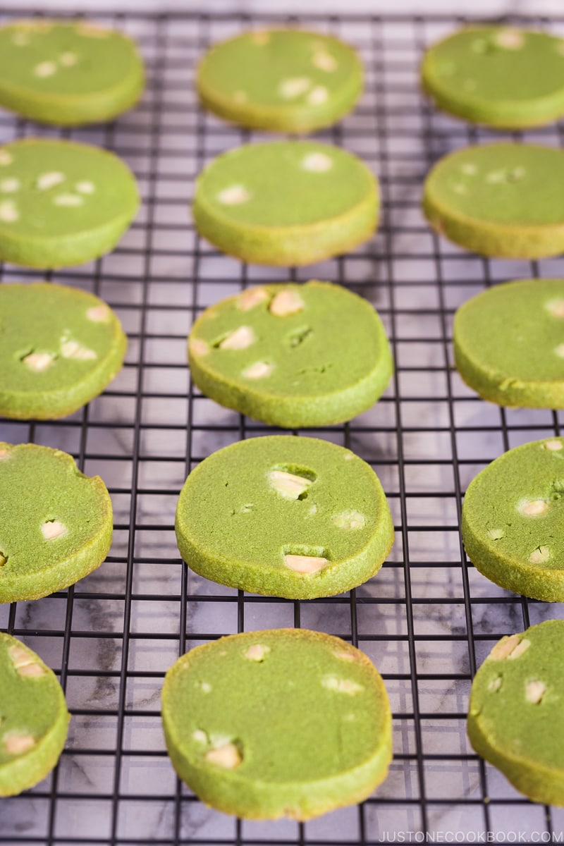 A wire rack containing matcha green tea cookies.