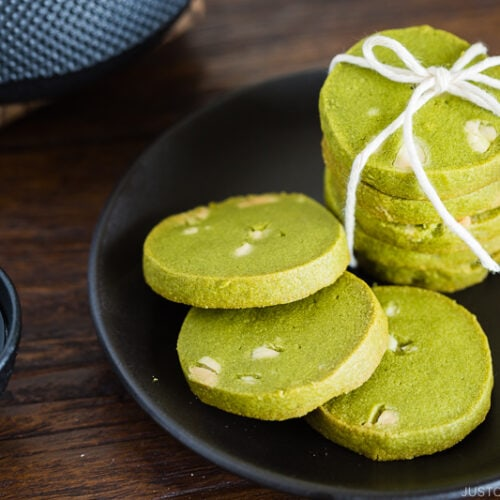A black plate containing matcha green tea cookies.