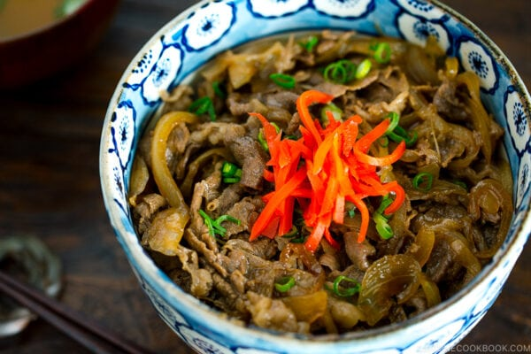 A bowl containing simmered beef over steamed rice.
