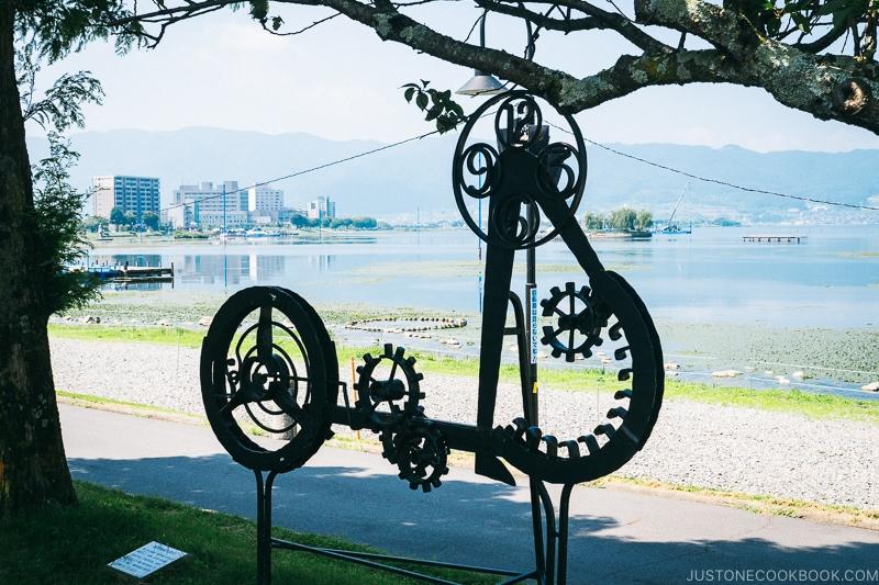 metal sculpture next to Lake Suwa