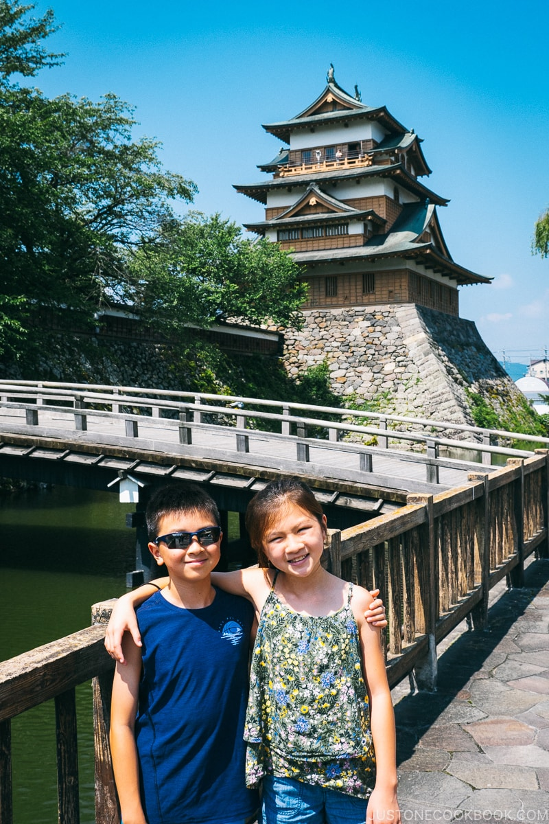 two children in front of a bridge with Takashima Castle in the back
