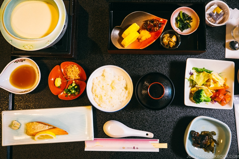 Japanese breakfast with rice, fish, soup, on top of a black tray