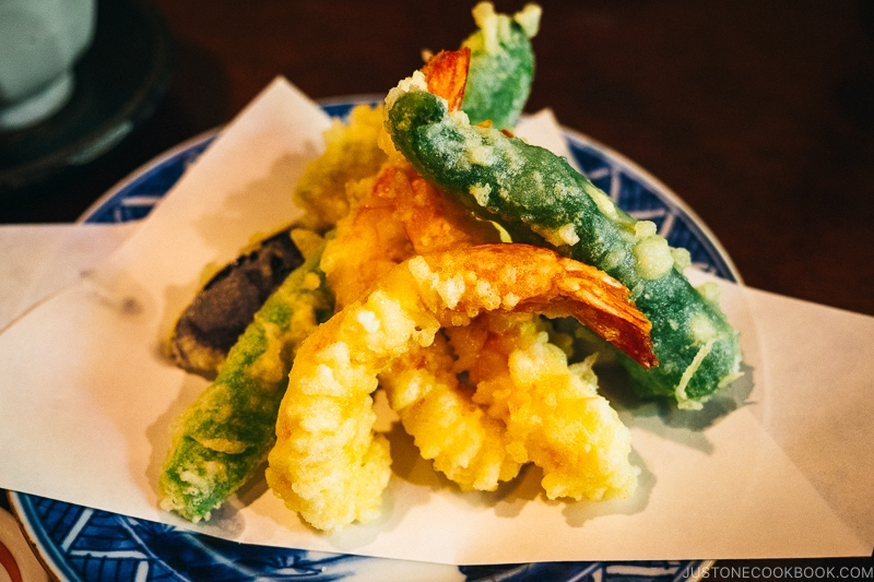tempura shrimp and vegetables on top of a blue plate