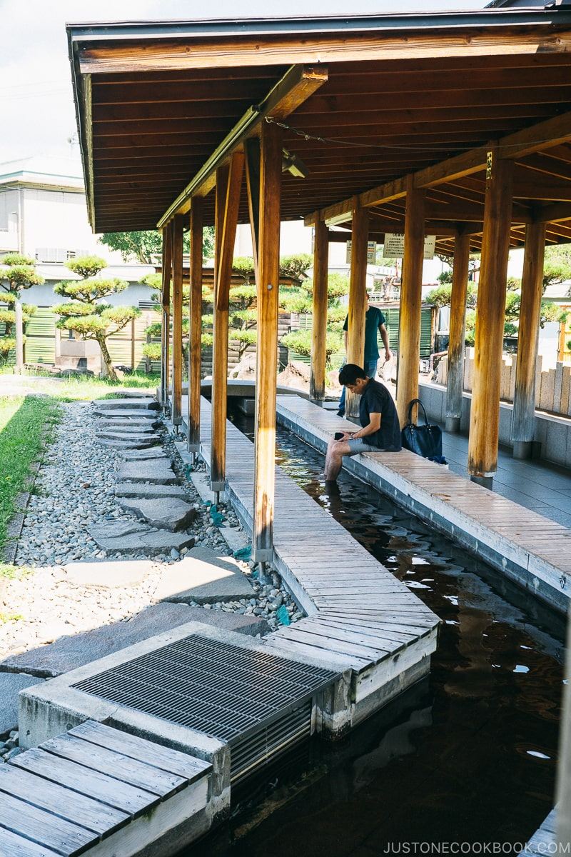 men soaking his feet in hot spring under a covered roof