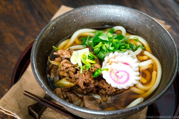 A bowl containing beef udon (niku udon) topped with fish cakes and simmered beef.