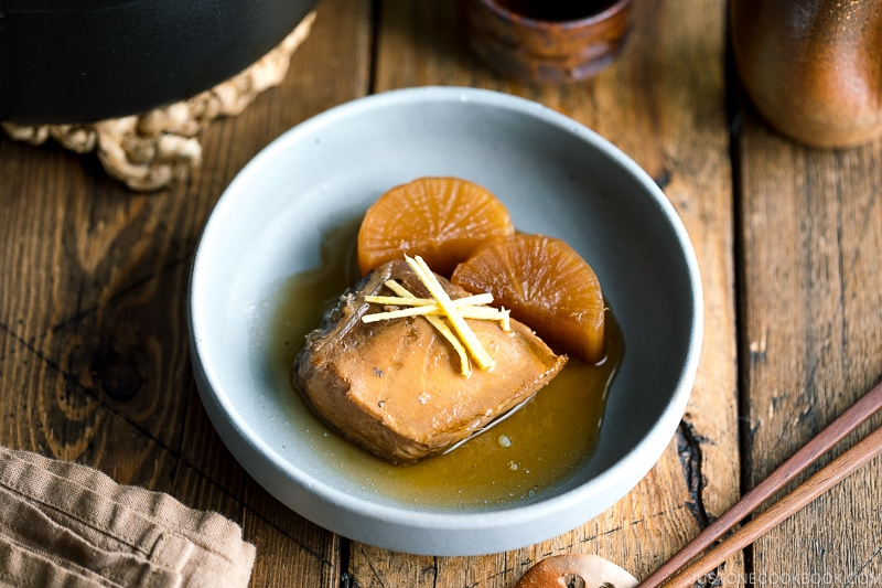 A grey bowl containing buri daikon, a simmered yellowtail and daikon radish, garnished with julienned ginger.