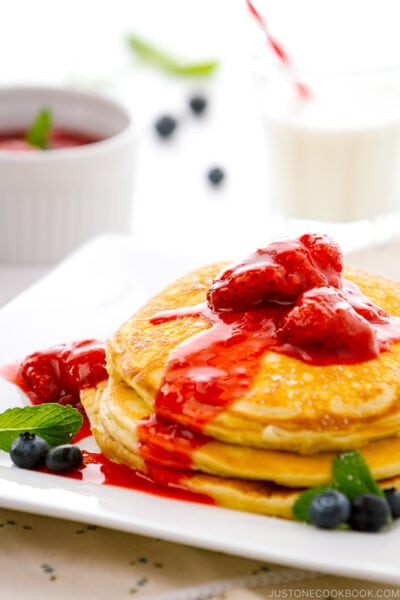 A dish containing Buttermilk Pancakes with strawberry compote.