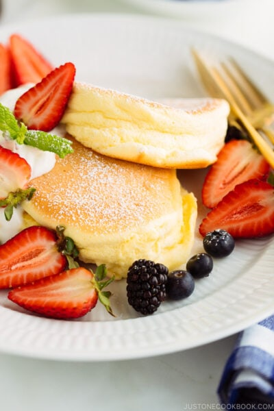 A white plate containing fluffy Japanese souffle pancakes.