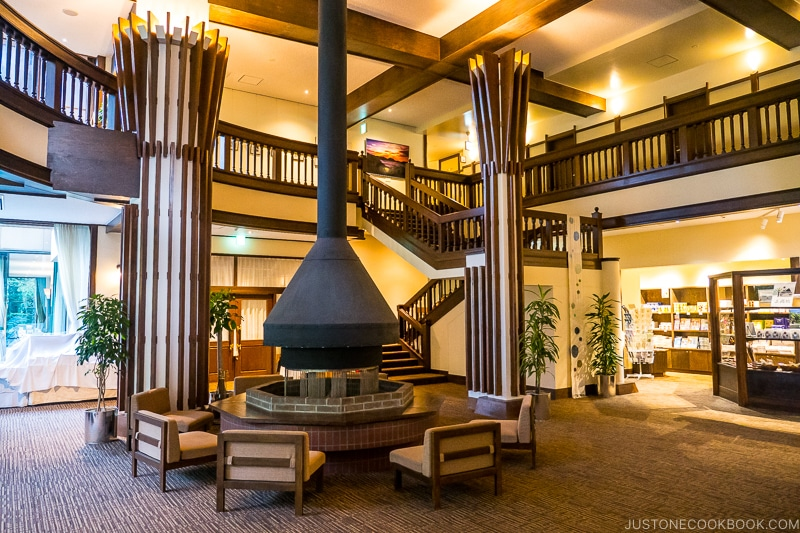 lobby of Kamikochi Alpen Hotel with wood burning firepit and stairs going to the second floor
