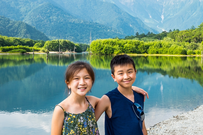 boy and girls standing next to Taisho Pond with mountain scenery in the back