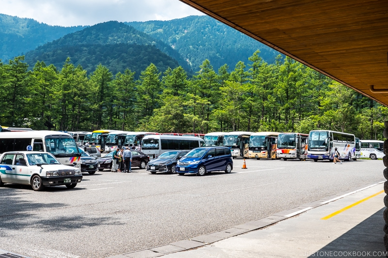 a parking lot with taxis and buses