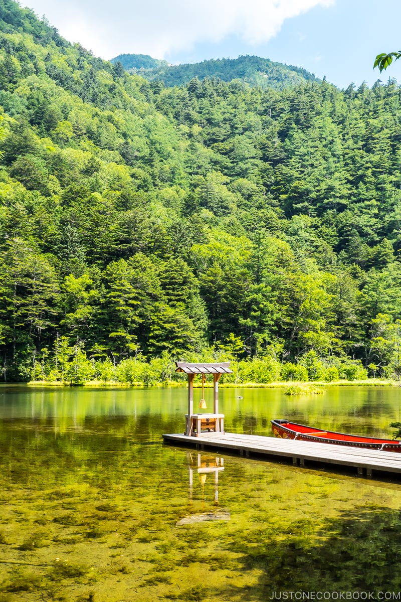 a praying altar at the end of the dock in the middle of a large pond with mountain in the back