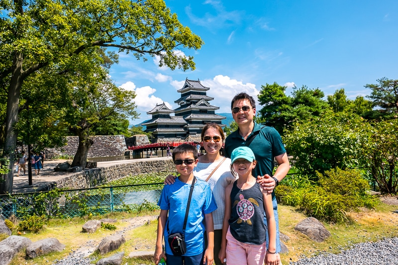 a family standing in front of Matsumoto Castle