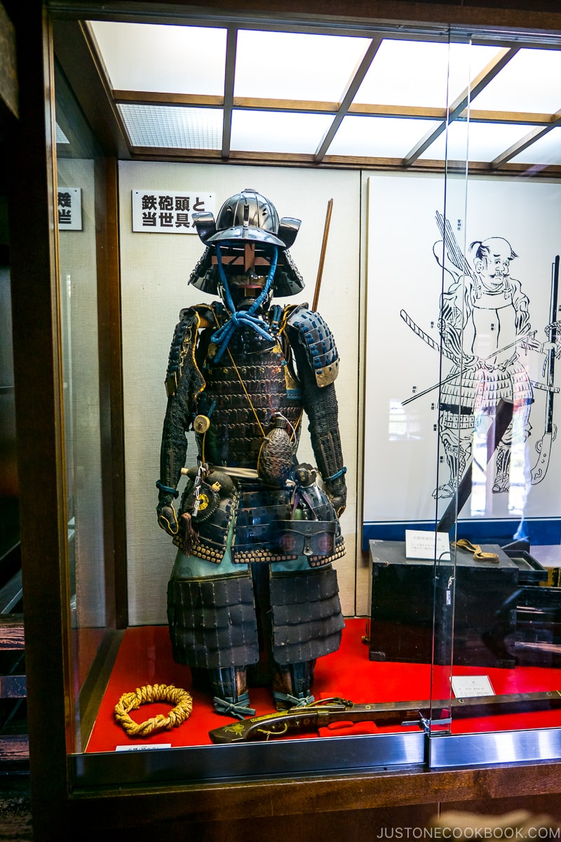 antique guns and armors in a glass display case