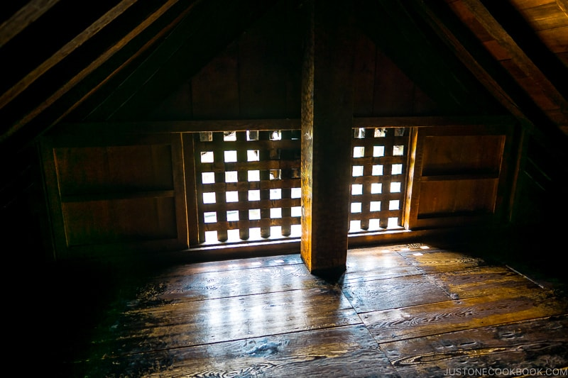 small room with wood floor and a window with cross bars