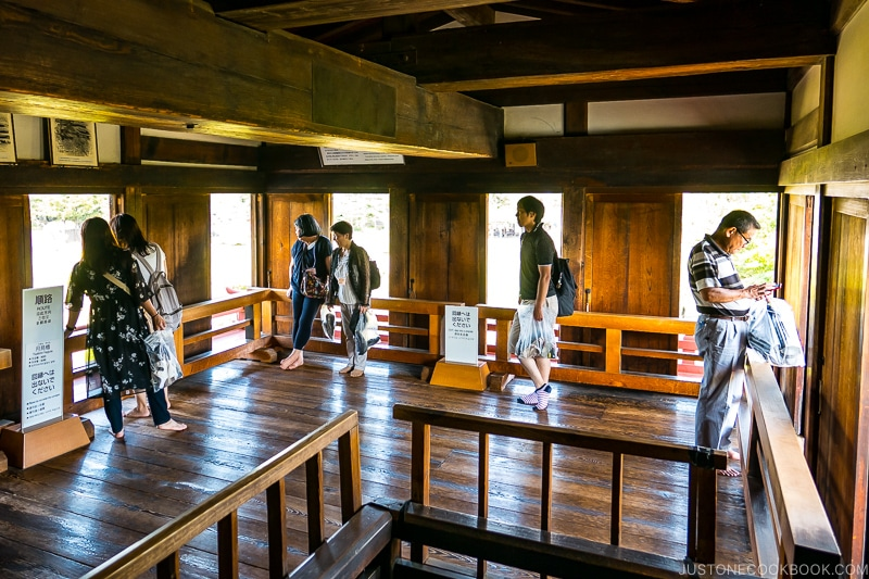 visitors on a wood viewing platform looking out windows