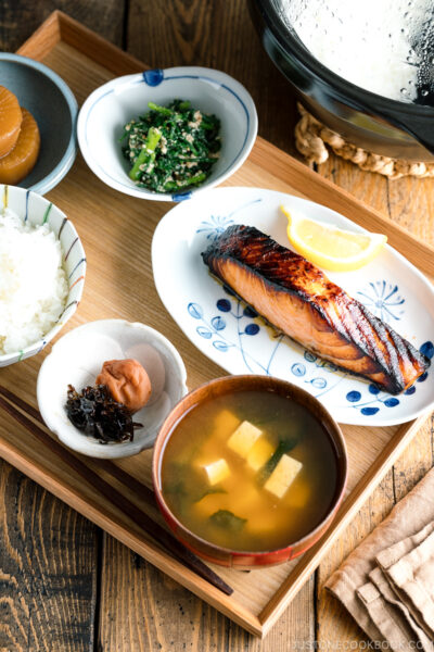 A Japanese meal set with shio koji salmon, miso soup, rice, and side dishes.