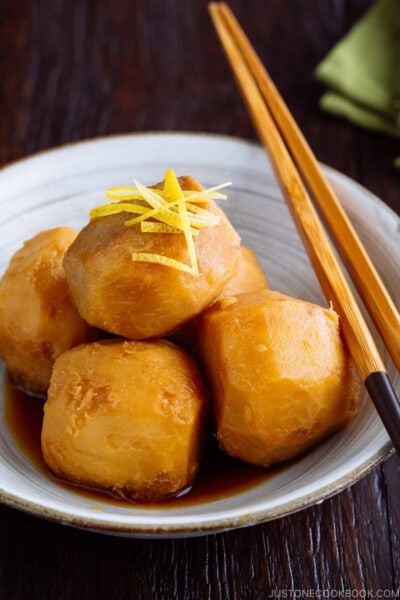 A white ceramic bowl containing simmered taro topped with julienned lemon zest.