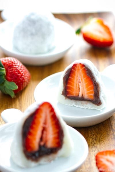 White plates containing strawberry mochi cut in half.