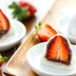 White plates containing strawberry mochi cut in half.