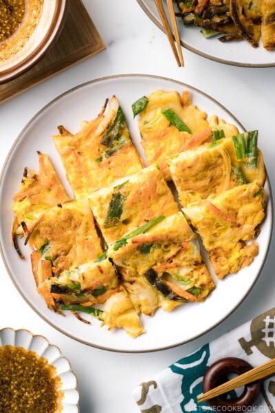 A white plate containing gluten free korean veggie pancake.