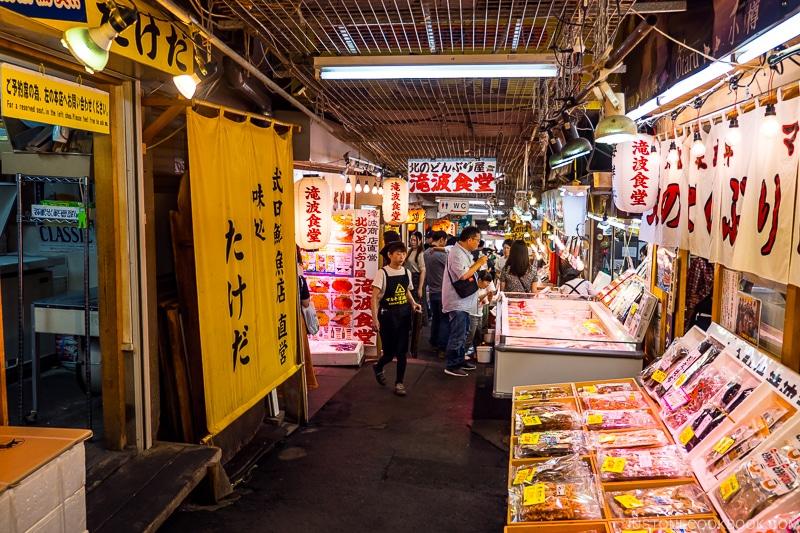 inside Otaru Sankaku Ichiba with a narrow walkway and restaurants on both side