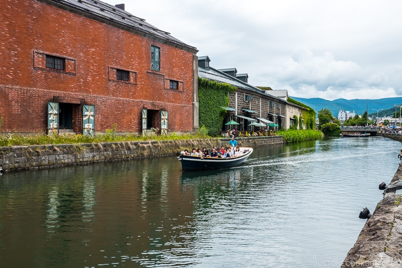 a boat cruising down Otaru Canal with warehouses in the background