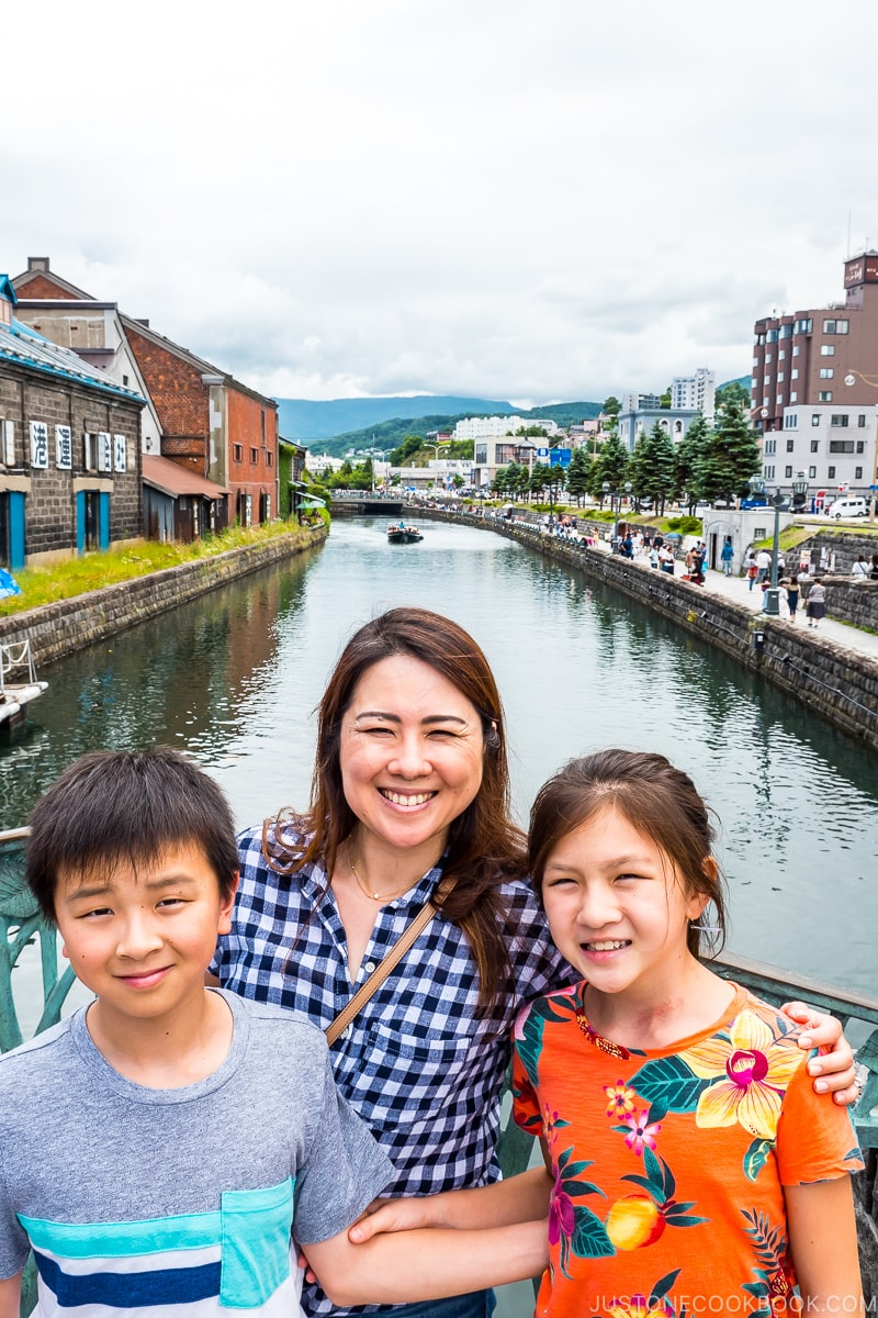 three people standing on a bridge on top of Otaru Canal